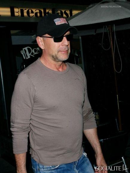 Bruce Willis, boné e óculos.