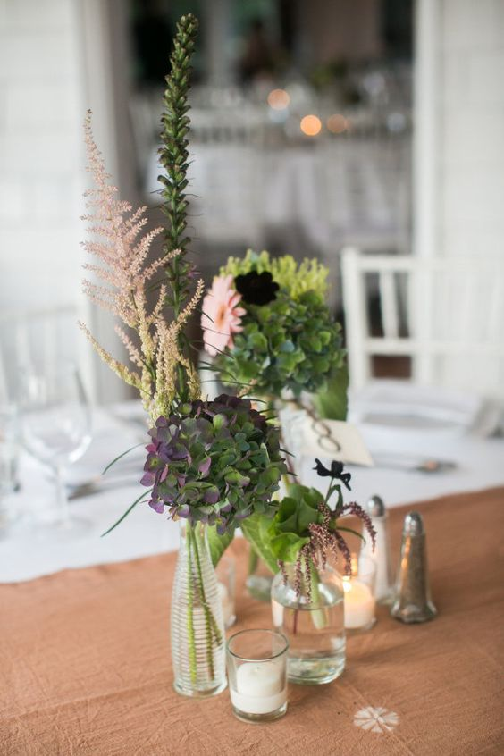 simple centerpieces with candles and assorted bottles