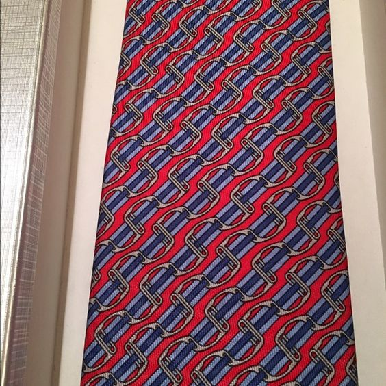 "Hermes Silk Tie NWT Hermes Silk Tie NWT attached. Comes in Bergdorf Goodman silver gift box. Tie is red, navy, and light blue. Gorgeous classic print. 100% Authentic Guaranteed. This is an XL size (about 3""-4"" longer then a standard tie) Hermes Accessories Scarves & Wraps"