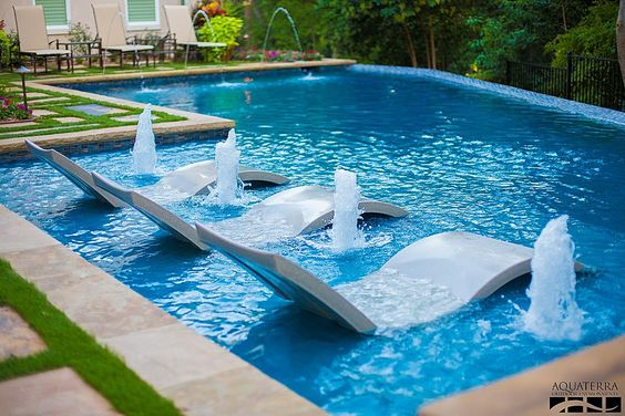 This pool has small sprays built right in and an infinity edge, but it's also got chairs you can relax in that are right there in the middle of the pool. Who wouldn't want to relax right here?