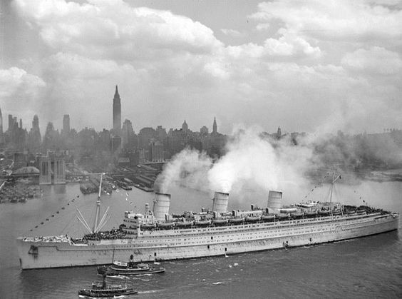 The British liner RMS Queen Mary arrives in New York harbour, 20 June 1945, with thousands of U.S. troops from Europe. The Queen Mary still wears her light grey war paint.
