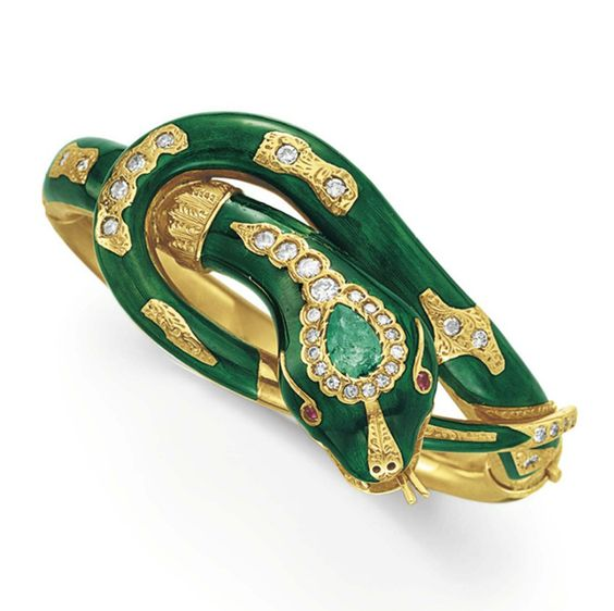A DIAMOND, GEM-SET AND ENAMEL SNAKE BANGLE BRACELET Designed as a green enamel snake, set at the head with a pear-shaped emerald and cabochon ruby eyes, with circular and single-cut diamond detail, mounted in gold, 2 3/8 ins. diameter: