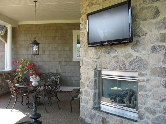 covered patio with a stone fireplace and tv. yes, please! - never gonna get it! :)