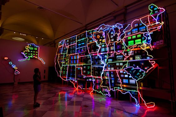 To design this monumental map of the United States, artist Nam June Paik arranged 336 televisions on a scaffold and overlaid it with almost 600 feet of neon. Fifty DVD players send multimedia simultaneously to screens populating each state. Approximately 15 x 40 ft.