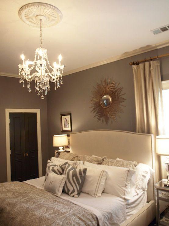 Beautiful bedroom design with gray walls paint color, Crate & Barrel Colette Bed, sunburst mirror, gray zebra pillows, crystal chandelier, black door and mirrored nightstands.