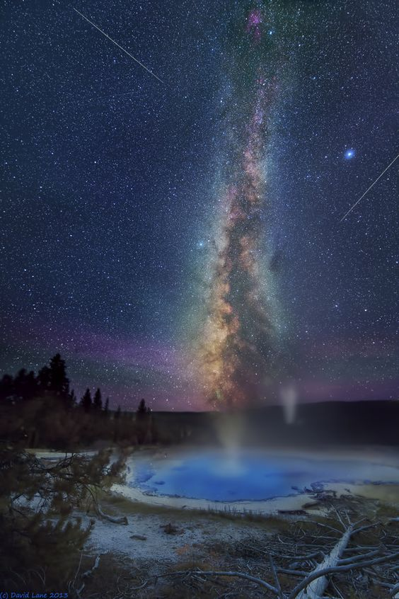 Solitary. Solitary Geyser in Yellowstone Park is anything but solitary this night. While it steams and erupts so does a large eruption from the Lion Group far below. Additionally 2 Perseid meteors flash across the vista. Two parallel faint satellite trails cross at about 11 o'clock.