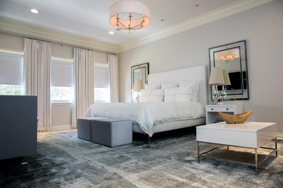 A silvery palette and reflective surfaces make this dreamy master bedroom feel as if it's resting on a cloud. Custom draperies draw to block light, and two upholstered ottomans serve as versatile, functional seating at the foot of the modern bed. The hand-loomed, banana silk rug features a soft shimmer, adding to the room's ethereal feel.