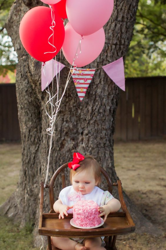 Adorable Smash Cake Setup - love the wooden highchair, balloons and bunting! #firstbirthday: