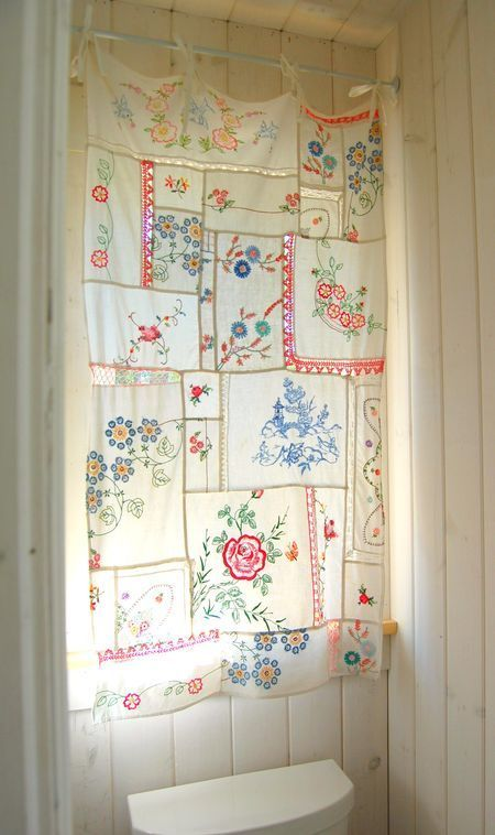 Vintage embroidered linens sewn together to make a curtain. Pieces of ribbon sewn at the top to attach it to the rod.: