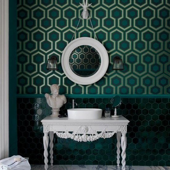 Green bathroom with geometric wallpaper. Sixties decadence is channeled through masculine graphic patterns in deep glossy teal. White classical furnishings pop against the dark background.