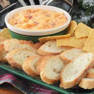 2 packages (8 ounces each) cream cheese, cubed  4 cups (16 ounces) shredded cheddar cheese  1 cup half-and-half cream  2 teaspoons Worcestershire sauce  1 teaspoon dried minced onion  1 teaspoon prepared mustard  16 bacon strips, cooked and crumbled  Tortilla chips or French bread slices