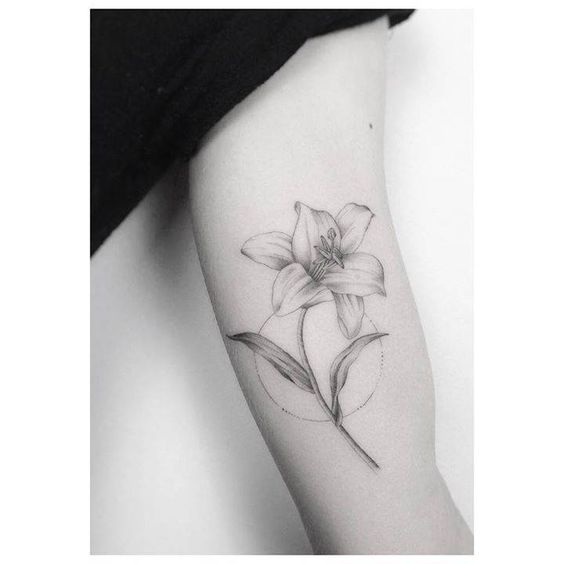 Fine line lily tattoo on the left inner arm.