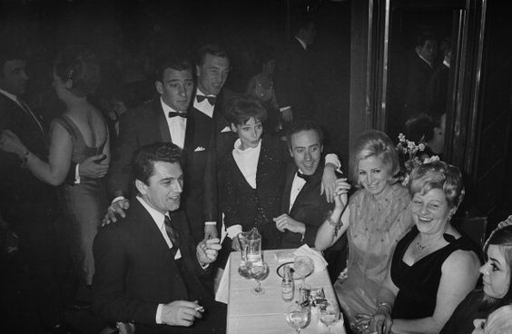 Frances Shea (1943 - 1967, far right) with her husband, English gangster Reggie Kray (1933 - 2000, standing, third from left) and celebrity guests at the El Morocco, a nightclub owned by the Kray Twins, in Soho, London, 30th April 1965. Kray has his hand on the shoulder of British actor Edmund Purdom (1924 - 2009). Behind Reggie can be seen his brother Charlie (1926 - 2000). At centre is Actress Adrienne Corri with her arm around Welsh actor Victor Spinetti (1929 - 2012). On his left can be…