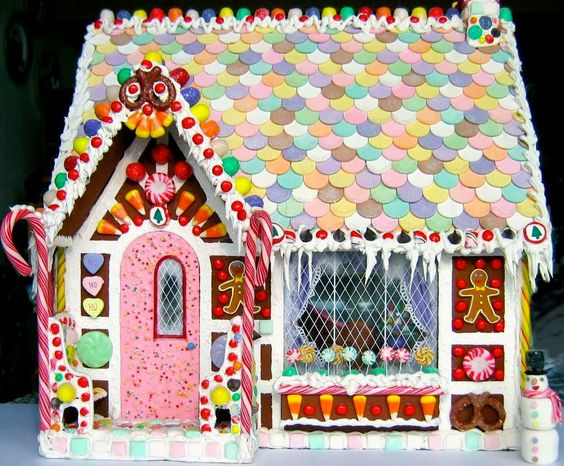 Fanciful gingerbread house with pastel wafers on roof and pink door