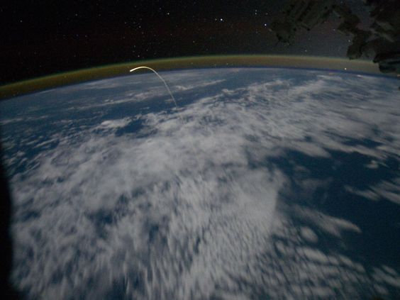 Space shuttle Atlantis leaves a glowing trail from the heat of re-entering the Earth's atmosphere on its way home.