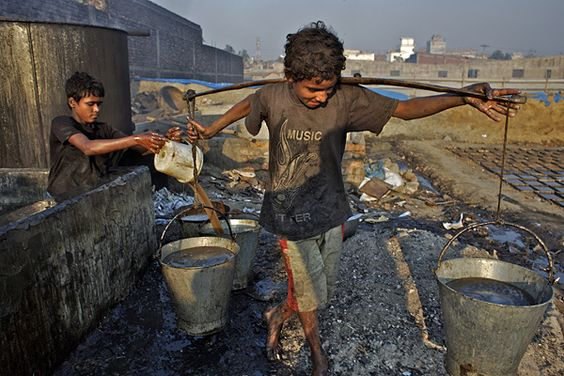 Nawab (age 12) and his friend Jabar make glue by boiling scraps of leather that they scavenged from debris, in Dhaka District of Bangladesh. The work – which exposes them to a myriad of toxic chemicals – earns each boy about 60 taka (approximately US 0.88) for each 13-hour shift. They are among nearly 215 million children involved in labour worldwide, of whom nearly 115 million work in hazardous conditions. © UNICEF/Shehzad Noorani  - To see more: www.unicef.org/photography