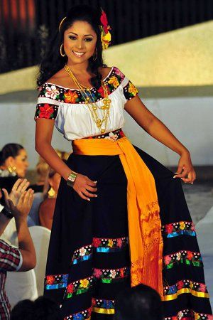 Here is another traditional mexican dress from the Tabasco region. It has beautiful stripes of embroidered flowers in vivid colors and a typical design that makes it look elegant with the black bottom and white top. As you can see the flower stripes are common with the chontal dress above, but they are used in very different confection styles.: