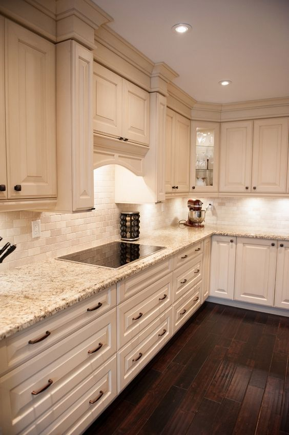 This White Kitchen Features Light Honey Hardwood Flooring And A Near Matching Island Countertop. photo - 2