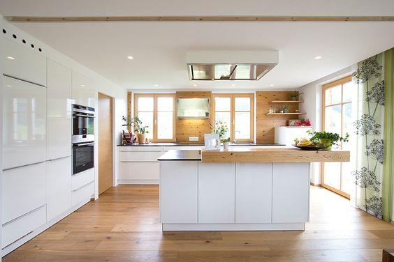 Küche weiß mit Altholzelementen und Eichenboden.