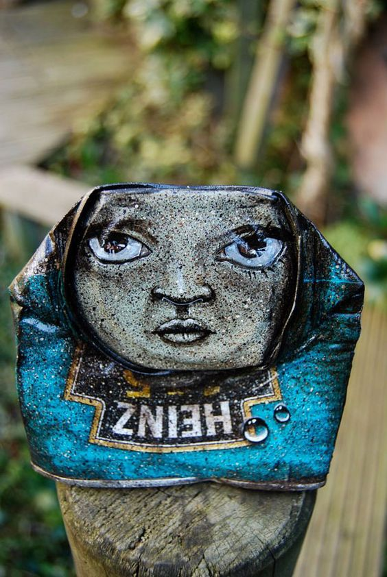 faces drawn onto discarded cans - my dog sighs