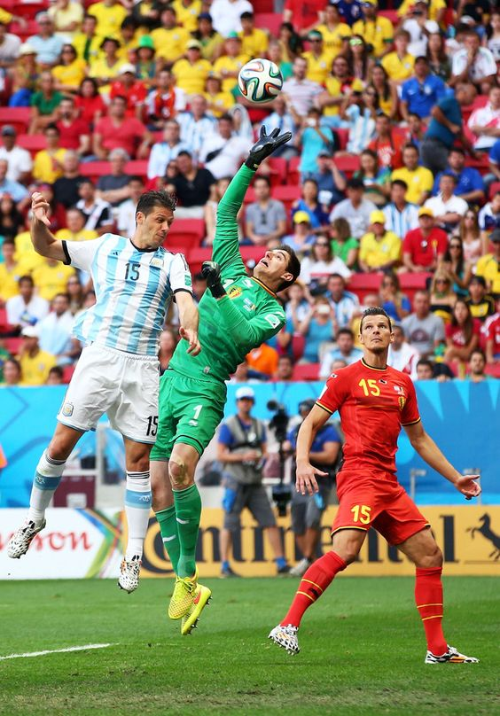 Thibaut Courtois of Belgium makes a save against Martin Demichelis of Argentina