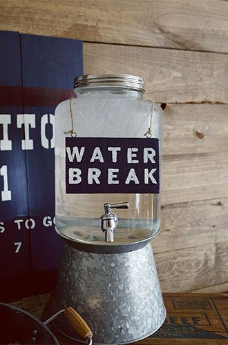 "Make sure guests don't forget to hydrate by providing a big vintage style cooler of water decorated with a stenciled ""water break"" sign.:"