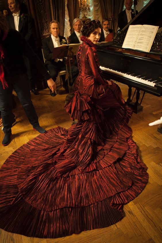 In Crimson Peak, the red dress (shown desaturated in this picture) instantly establishes Lady Lucille as being different from the pastel-clad partygoers (including Edith) and associates her with blood.: