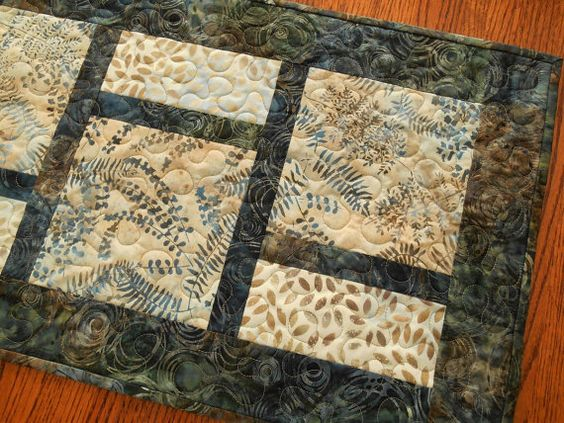 Batiks in beautiful shades of blue mix with browns and cream in this modern quilted table runner. The two lighter prints feature a variety of leaves and the darker print has abstract circles and adds hints of green.  The size is approximately 14 X 45 (36 X 114 cm) - a versatile size for use on a dining table, buffet, coffee table or a bedroom dresser.  I machine-quilted an all-over meander in taupe colored thread. On the back I used another batik print with dotty lines in soft shades of…