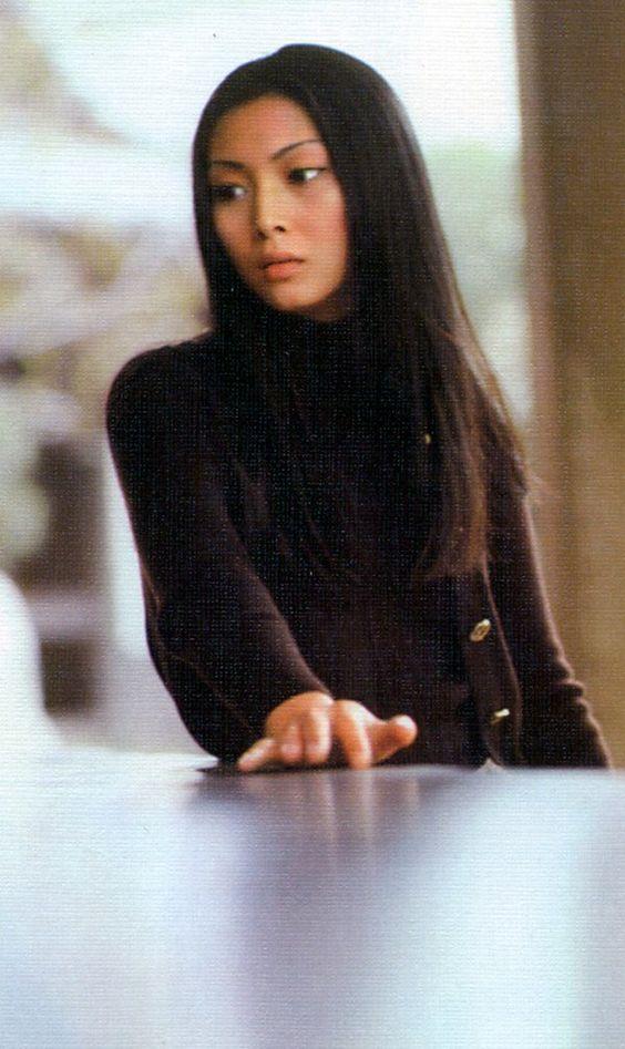 黒いセーターを着てテーブルに手をついている梶芽衣子の画像