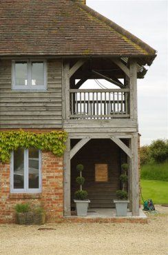 2-storey barn house in Oxfordshire with handmade brick walls, plain clay tile roof and exposed English oak frame