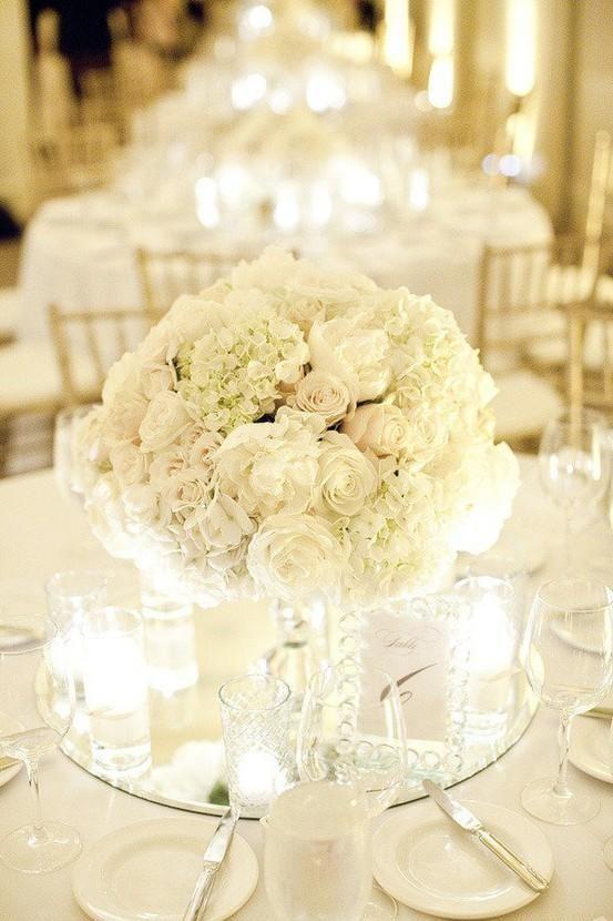 Short White Centerpiece On Round Mirror Makes The Perfect Accent To Your Tabl Flower Centerpieces Wedding Wedding Flower Arrangements White Wedding Decorations