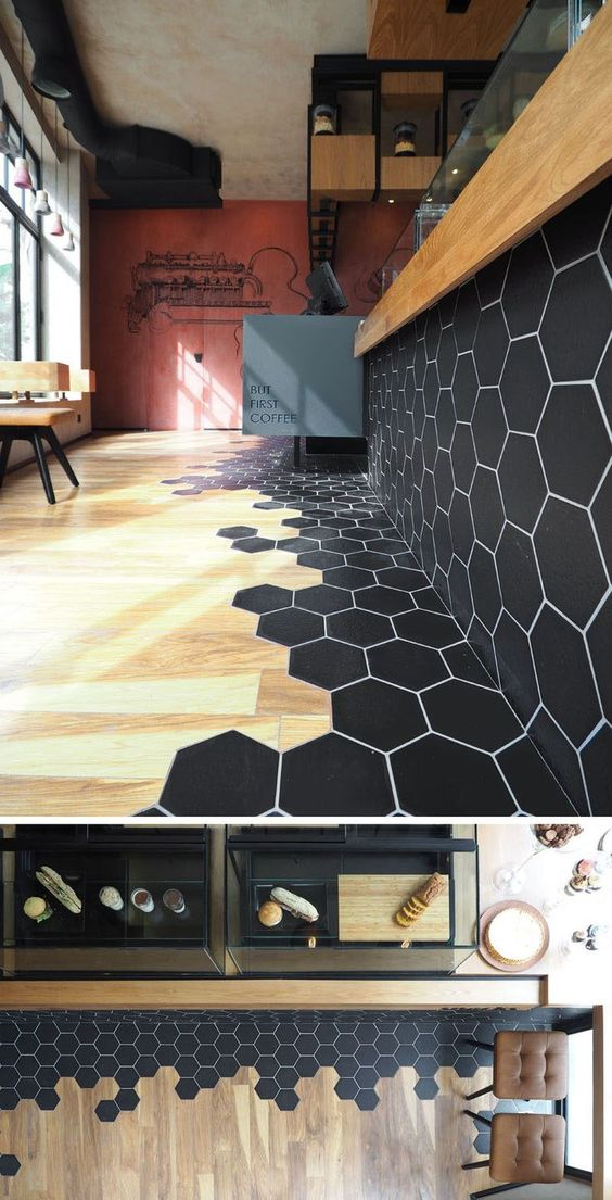 Black hexagon tiles and wood laminate flooring are a design element in this modern cafe.: