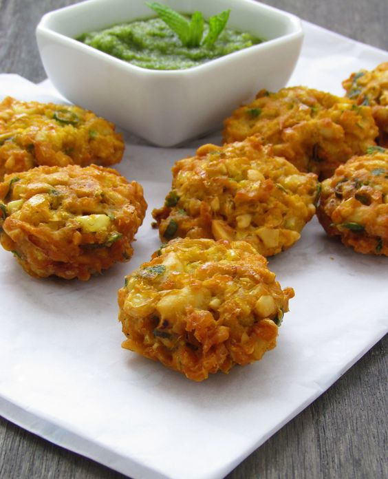Corn-Peanut Fritters With Mango-Mint Chutney       2 cups fresh white corn kernels 1/2 cup raw peanuts, 3 scallions, 3 Thai green chillies 1 fat garlic clove, 2 tbsp cilantro/parsley,  1 tsp garam masala 1/2 tsp roasted cumin powder 1 tsp amchoor 1/2 tsp turmeric powder 1 tsp kasoori methi  6 tbsp besan Salt to taste Oil for frying