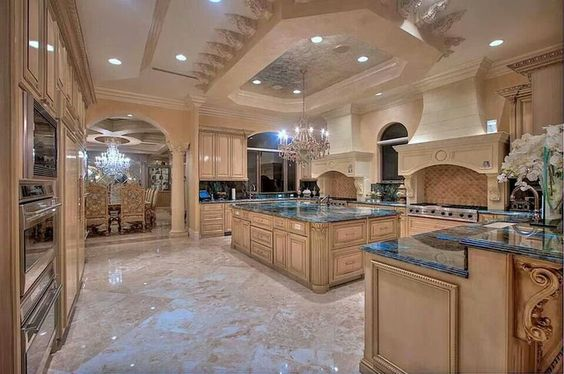This giant kitchen has plenty of cupboard space, a large chandelier, elegant styling and a whole lot more. With the marble floors and giant stove you've got something super high end here.
