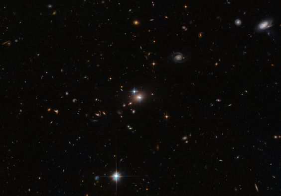 In this new Hubble image two objects are clearly visible, shining brightly. When they were first discovered in 1979, they were thought to be separate objects — however, astronomers soon realized that these twins are a little too identical! They are close together, lie at the same distance from us, and have surprisingly similar properties. The reason they are so similar is not some bizarre coincidence; they are in fact the same object.