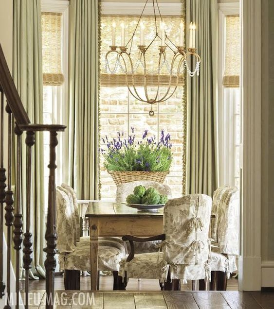 French Country decor in a dining room with slipcovered dining chairs, lavender, and breathtaking interior design. #Frenchfarmhouse #frenchcountrydecor #frenchcountrystyle #diningroomdecor #interiordesign #toile #provence #lavender #milieu #slipcover