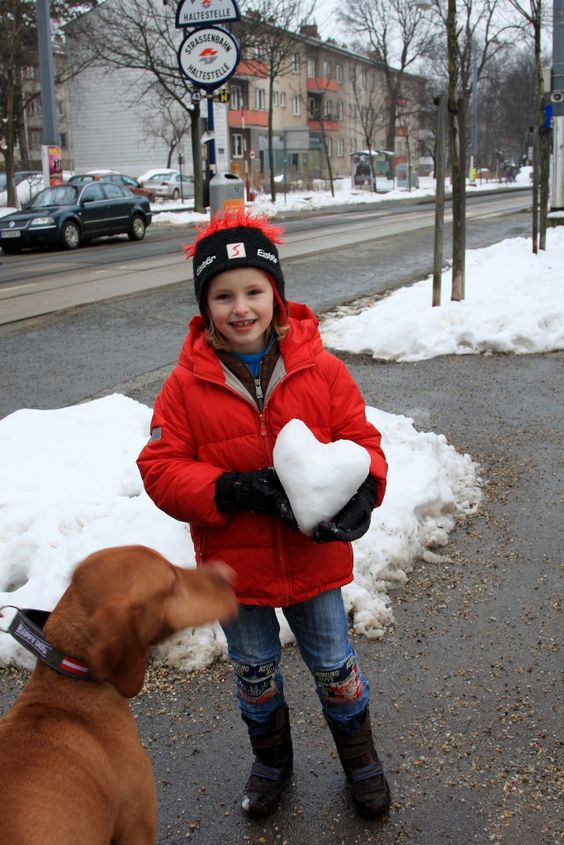 On foot, we found an adorable girl is walking on the street of Neuwaldweg carrying a snow heart. Feb. 15. Austria