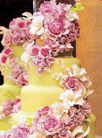 Floral Cake  A yellow wedding cake with pink flowers.