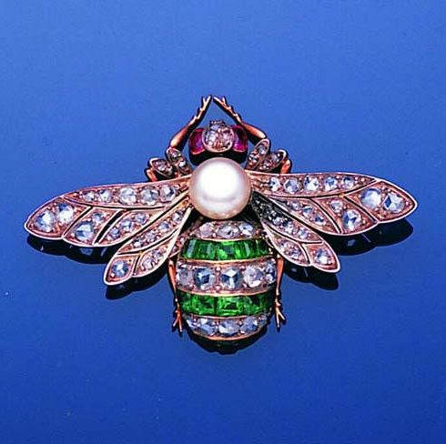 A late 19th century diamond, ruby, emerald and pearl bee brooch, circa 1890  The abdomen set with rows of calibré-cut emeralds and rose-cut diamonds, with a bouton pearl thorax and oval-shaped ruby eyes, the outstretched wings pierced and set with rose-cut diamonds, detachable brooch fitting, width 4.7cm.