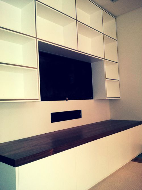 tv fitted into wall recess with bookcase shelving surround and low sideboard with storage bespoke wall storage