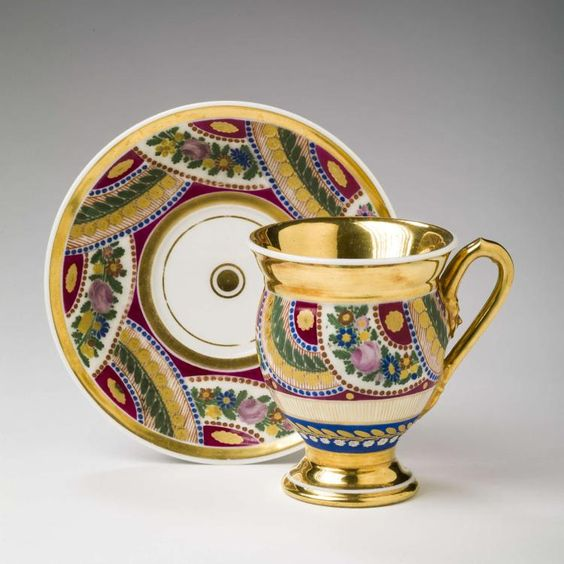 RUSSIAN PORCELAIN CABINET CUP AND SAUCER, 1815-25. Painted with overlapping semicircular bands of lush floral garlands alternating with vines and fiddleheads, within beaded borders and enclosing gilt flowerheads, the cup surrounded by a flowering vine above the foot and partly-gilt on the interior, the handle with mask and berry terminals.