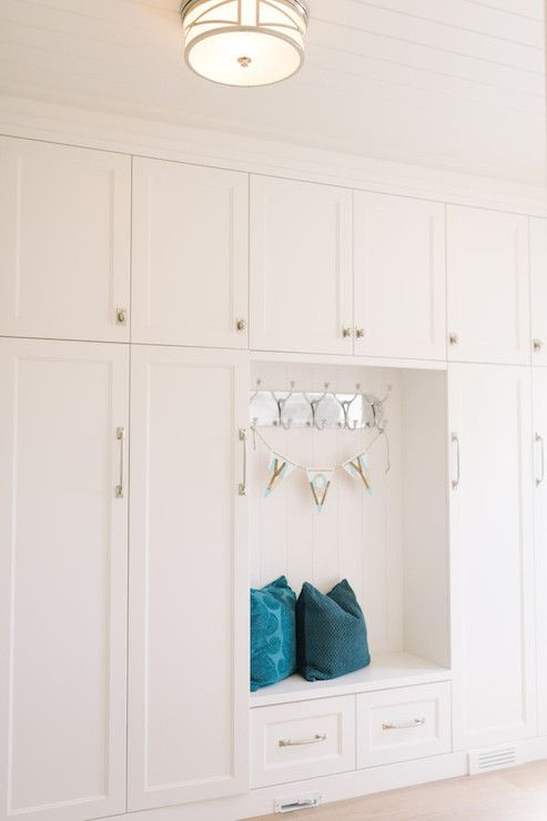 All-white mud room boasts tongue and groove clad ceilings illuminated by a round brushed nickel ...