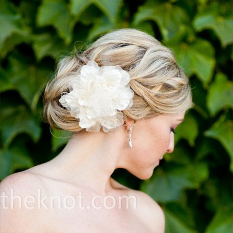 hair in a low bun with a silk flower set on one side.
