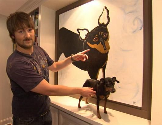 "Eric Church shows off a portrait of his dog, Quincy Jones, hung just outside the master bedroom of the 4,000 square foot home he shares with his wife, music publisher Katherine Blasingame. Church jokes about the tiny pooch, ""We can't put her down cause she'll chew people's legs off. She's a vicious beast."" (Courtesy CMT )"