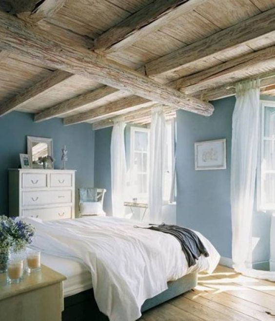 A seaside blue effortlessly complements the rustic details of this charming cottage bedroom. Sheer white linens impart a carefree touch to the windows while the whitewashed finish of the furnishings bring in a cohesive element to the space. Smokey Azurite, Sherwin Williams.