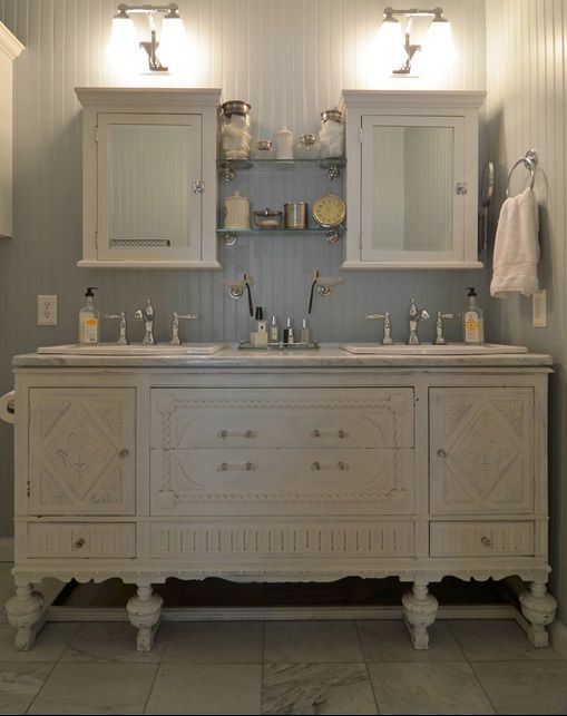 A bathroom vanity, white and antique, with white vanity cabinet mirrors above and matching ...