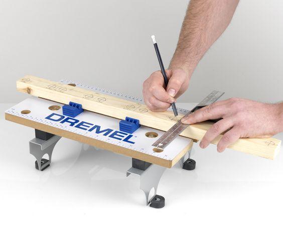 Con Dremel TRIO e la punta da taglio multiuso, tagliare le spine di legno in 12 pezzi di 22 cm. Sui due listelli di legno tagliati per la parte frontale e posteriore, misurare e segnare i dodici punti in cui posizionare le spine: segnare un punto ogni 10 cm. All'interno delle tacche da 10 cm, segnare una tacca a 1,5cm e a 8,5 cm. Questa sarà la posizione centrale in cui inserire le spine. Verificare che dall'estremità in basso del listello al centro delle spine vi sia una profondità di 1,5…