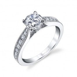 This captivating designer engagement ring features a 1 carat round solitaire diamond nestled between the uplifting shoulders of the tapered shank decorated with graduated round brilliant diamonds in a channel setting and edged with milgrain accents.  The total carat weight of this intricate engagement ring is 0.34.