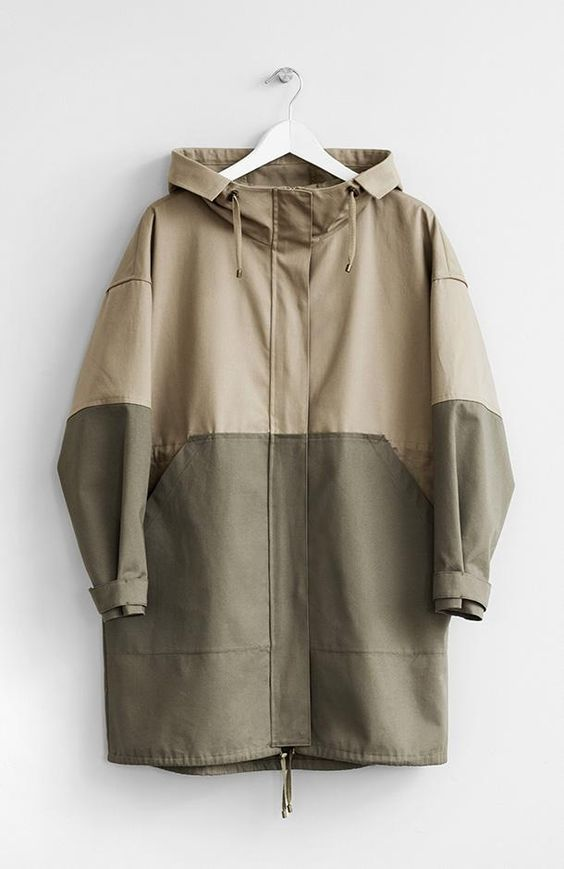 Fabric: 100% CottonColor: Beige and KhakiCare: Machine Wash Cold/ Tumble Dry Low Two-tone hooded oversized parka with two front pockets. Centre front zipper closure. Unlined. 85 cm long. Made in USA.