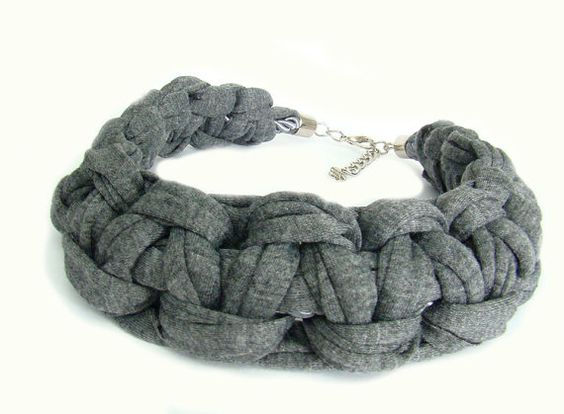 Made by knotting smoky grey t-shirt yarn. The two ends are secured with silver tone end caps and closed with a lobster clasp. The necklace measures